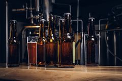 Free Bottles And Glass Of Craft Beer On Wooden Bar Counter At The Indie Brewery. Royalty Free Stock Photos - 128157598
