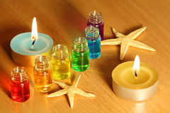 Bottles with aroma oils, candles and starfish. Row of six bottles with colored aroma oils, candles and starfishes on table Stock Photography