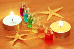 Bottles with aroma oils, candles and starfish. Row of six bottles with colored aroma oils, burning candles and starfishes on table Royalty Free Stock Image