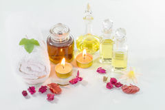Bottles of aromatic oils with candles, flowers, towel on glossy white table Stock Photos