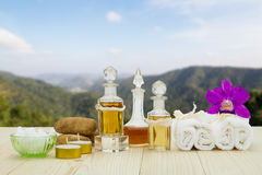 Bottles of aromatic oils with candles, pink orchid, stones and white towel on vintage wooden floor on blurred mountain background Royalty Free Stock Image