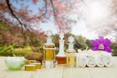 Bottles of aromatic oils with candles, pink orchid, stones and white towel on vintage wooden floor on lake and forest background Stock Image