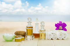 Bottles of aromatic oils with  candles, pink orchid, stones and white towel on wooden floor on blurred beach and sky background Stock Images