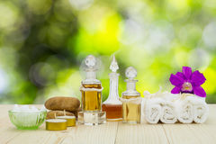 Bottles of aromatic oils with candles, pink orchid, stones and white towel on wooden floor on blurred green bokeh background Stock Image