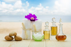 Bottles of aromatic oils with  pink orchid, stones and white towel on vintage wooden floor on blurred beach with cloudy blue sky Royalty Free Stock Photos