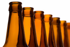 Bottles arranged in line. Line of beer bottles, backlit technique Royalty Free Stock Image
