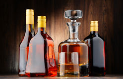 Bottles of assorted alcoholic beverages and glass of whisky Stock Photos