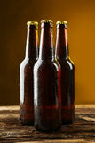 Bottles of beer with drops on a brown wooden background Stock Image