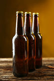 Bottles of beer with drops on brown wooden background. Stock Image