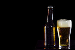 Bottles of beer and glass getting cool on black background. A Bottles of beer and glass getting cool on black background stock photo