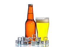 Bottles of beer and glass getting cool in ice cubes on white. A Bottles of beer and glass getting cool in ice cubes on white background stock photos