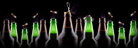 Bottles of beer on ice. On black background Royalty Free Stock Photos