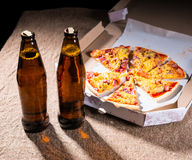 Bottles of Beer and Pizza in Box on Table Royalty Free Stock Image