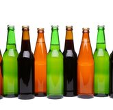 Bottles of beer in row. Different bottles of beer in row on the white background Royalty Free Stock Photos