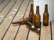 Bottles and bin on wooden floor Stock Images