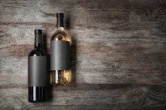 Bottles with blank labels on wooden background. Mock up for design stock photo