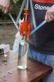 Bottles bottling. Man using corker for bottling bottles Stock Photography