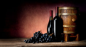 Bottles with cask and grape Royalty Free Stock Photography