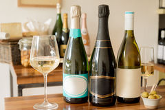 Bottles of Champagne with Blank Labels Between Wineglasses and Olives Stock Photos
