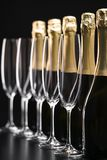 Bottles of champagne and empty glasses on a black background. Se. Perspective view detail of golden champagne bottles and empty glasses. Selective focus stock images