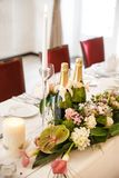 Bottles of champagne, flowers and candles on the wedding table.  Royalty Free Stock Photo