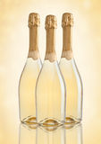 Bottles of champagne golden yellow color on golden. Background stock image