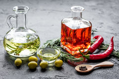 Bottles with chili and olive oils and herbs on stone background Stock Photography