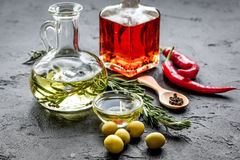 Bottles with chili and olive oils and herbs on stone background Stock Photos