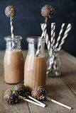 Bottles of chocolate milk with straws and cake pops Royalty Free Stock Photos