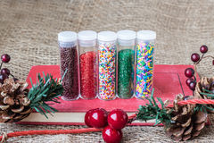 Bottles of christmas candy sprinkles with burlap background and pine cones Royalty Free Stock Images