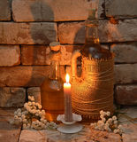 Bottles of cider with candle. Two bottles of cider wine with burning candle and white flowers in castle background Stock Images