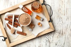 Bottles with cinnamon oil, powder and sticks. On wooden tray Royalty Free Stock Images