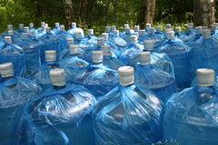 Bottles of clean water in the forest. The rows of bottles of clean water in green forest Stock Photography