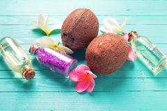 Bottles with coconut oil, coconuts  and sea salt  on  bright  wo Royalty Free Stock Photo