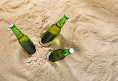 Bottles of cold light beer on sand with copy space Stock Images