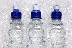 Bottles of cold mineral water on crushed ice. Photo of cold mineral water in plastic bottles on crushed ice royalty free stock photos