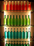 Bottles in color. Multi-colored bottles on glass shelves Royalty Free Stock Image