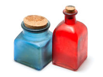 Bottles of colored glass on a white background. Bottles of red and blue glass stand on white background royalty free stock photos