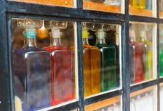 Bottles with colored liquid on the window Stock Photos