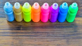 Bottles with colorful dry pigments on wooden background. Rainbow colors  - colorful circle - copy space Stock Photos