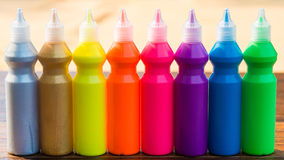 Bottles with colorful dry pigments on wooden background. Bottles - in a row - with colorful dry pigments on wooden background - rainbow colors Royalty Free Stock Photography