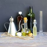 Bottles with cooking oil, vinegar and wine on wooden table. Stock Image