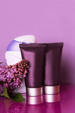 Bottles of cosmetics with lilac flowers. Some bottles of cosmetics with lilac flowers over violet stock image