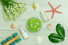 Bottles with cream for face skin and aromatic oil, hand massager, bowl with sea salt, starfish, sea shell and bouquet of lilies o royalty free stock photo