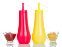 Bottles, cups with ketchup and mustard isolated on white. Royalty Free Stock Photography