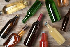 Bottles with different alcoholic drinks. On wooden background, flat lay stock photo