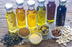 Bottles with different kinds of vegetable oil. On the wooden table stock photo