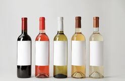 Bottles of delicious wines with blank labels on white background. Bottles of different wines with blank labels on white background royalty free stock image