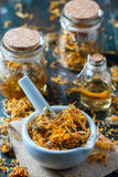 Bottles and dried calendula officinalis petals with macerated oil on wooden background. Stock Photo
