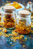 Bottles and dried calendula officinalis petals with macerated oil on wooden background. Stock Photography